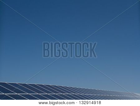 A long row of solar panels generating clean, renewable electricity under a clear, blue sky.