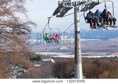 January 15, 2015. Chair lift with skiers the background mountains. Sunny winter day. Resort Valchanskaya Valley. Tatra. Slovakia. Healthy sport lifestyle.
