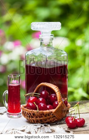 Glass of cherry brandy liqueur with fresh maraschino cherries in the basket