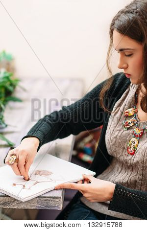 Female beautiful designer at work. Young woman draws dress sketch at the table. Intently designer working on dress sketch close-up