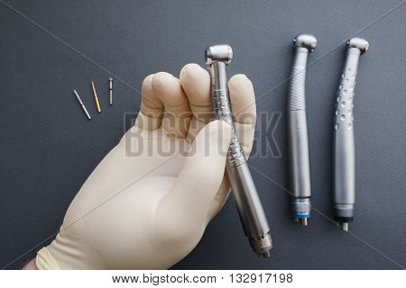 Hand of dentist in latex protective gloves holding dental drill handpiece. Flat lay of dental handpiece in dentist hand on gray background. Dental handpieces and bur tools on background