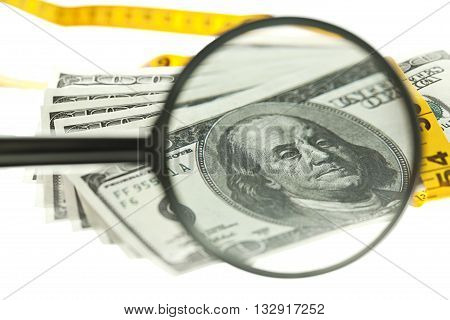 dollars with measuring tape and magnifying glass