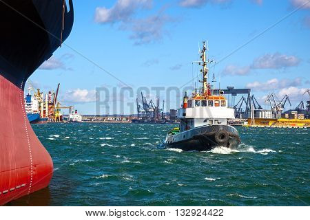 A cargo ship with the assistance of a tugboat in port.