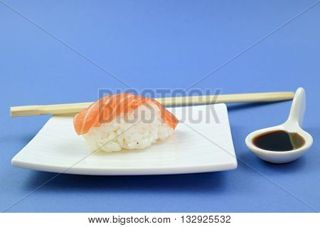 sushi, soy sauce and chopsticks on blue background