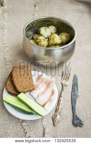 Boiled new potatoes with herbs in a pan. Lard, rye bread and cucumber are on a plate.