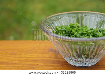 Chopped chive in a glass bowl on wooden table