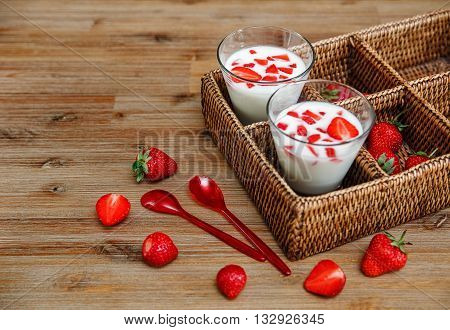 Two Glasses of Yogurt,Red Fresh Strawberries in the Rattan Box with Plastic Spoons on the Wooden Table.Breakfast Organic Healthy Tasty Food.Cooking Vitamins