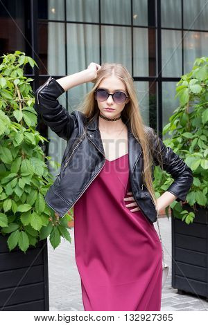Young pretty blond girl dressed in leather jasket like rockstar