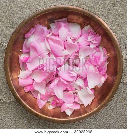 Pink rose petals in a copper plate