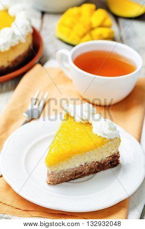 mango cheese cake decorated with whipped cream and mango puree