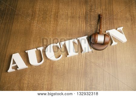 Top view of auction gavel on wooden desktop