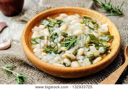 Rosemary white bean spinach soup on wooden background