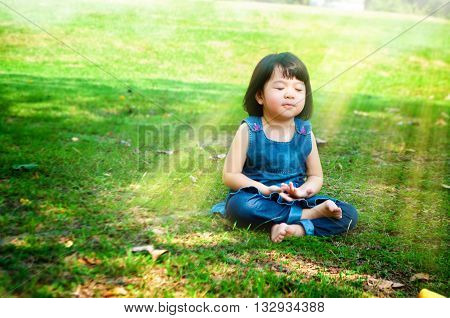 Little asian girl practicing mindfulness meditation outdoor in a park.