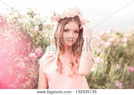 Smiling teenage girl 14-16 year old with curly hair and wreath of roses outdoors. Looking at camera. Romance.