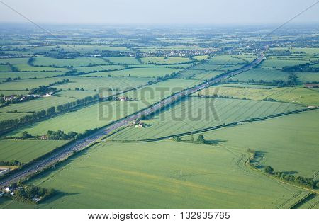 view over the early summer green fields and a dual carriageway road from the air; East Anglia; UK