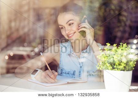 Business moments. Cheerful and glad modern young woman talking on a smartphone and sitting near a window in a cafe while writing something in her copybook