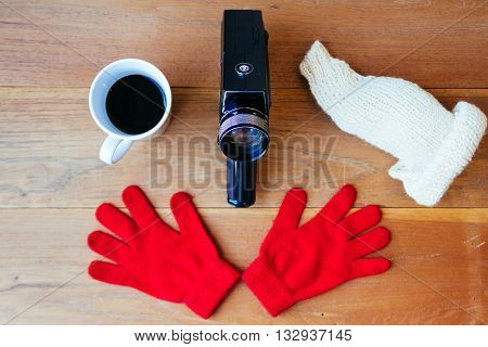 Super-8 film camera with a cup of coffee, gloves and wool hat on wooden boards