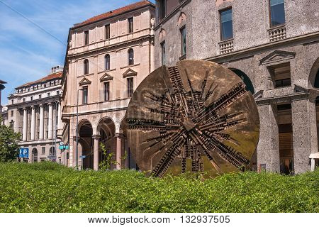 Milan Italy - May 25 2016: Disco abstract bronze circular sculpture with contemporary value by Arnaldo Pomodoro on Piazza Meda created in 1980