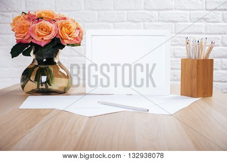 Roses in vase blank picture frame paper sheets and pencils on wooden desktop and white brick wall background. Mock up