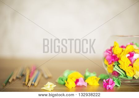 Glass bowl and wooden desktop with crumpled paper and pencils on blurry background