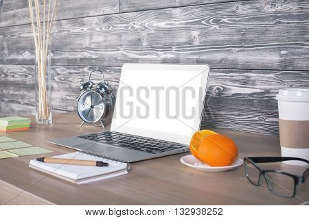 Side view of office desktop with blank white laptop notepad orange on saucer coffee cup alarm clock and stickers. Mock up
