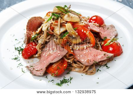 Asian creative food. Whole grain brown vermicelli noodles with mushrooms, vegetables, sun-dried tomatoes and sliced veal meat . Chinese or Korean healthy food. Restaurant dish closeup.