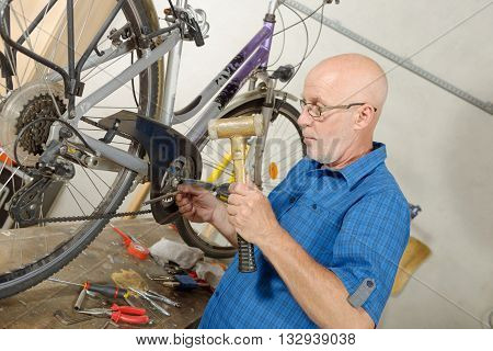 a man repairing bicycle in his workshop.