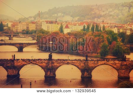 Center of Prague city at autumn with red roofs and Charles Bridge over river Vltava, european travel landscape background in vintage style