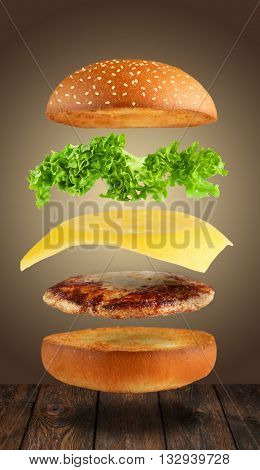 Burger ingredients. Cheeseburger. Separated burger ingredients at wood. Hamburger explosion. Cheeseburger flying layers at brown background. Levitation of burger and cheese, meat, lettuce.