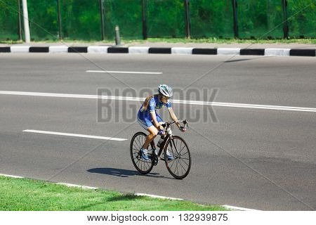 Cycling road. Sport bicycle. Woman cycling on countryside summer road or highway. Female training for triathlon or cycling competition. Highway cycling.