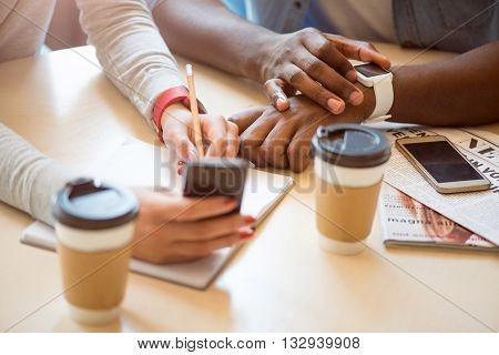 Tension is in the air. Modern young people sitting in a cafe and drinking coffee while using their smart watch and phone and writing some details down