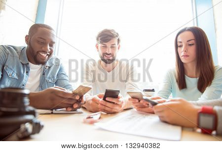 On top of trends. Cheerful and glad modern young people holding mobile phones in their hands and typing sms while being in a cafe