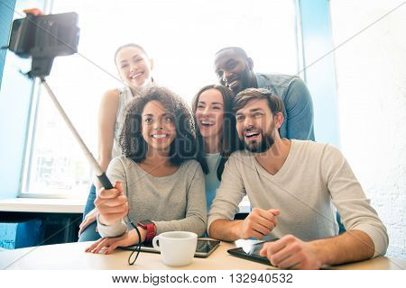 Friendly team. Smiling and cheerful modern young people sitting in a cafe while drinking coffee and using a smartphone and a selfie stick to take selfie photograph
