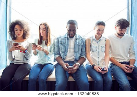 Up to date leisure. Positive and merry group of young people using their cell phones while sitting on a window sill and typing text messages