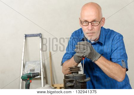 a man with a car generator in his workshop