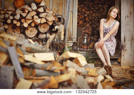 romantic barefoot girl sad seated near firewood