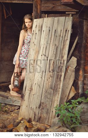 romantic sad girl with a gas lamp in the barn background