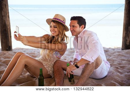 Attractive young couple taking a selfie with a smartphone while enjoying their vacation at the beach relaxing and drinking some beer together