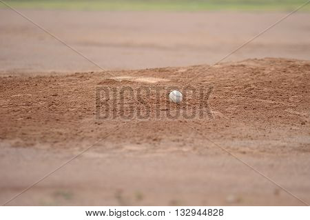Baseball sitting on the pitching mound dirt.