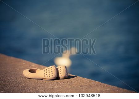 Beige female summer shoes on sea shore. Footwear.