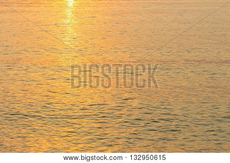 Soft focus sea water nature background image variety of colors and hues of the rising sun light Reflections on the sea in the morning :ideal use for background: