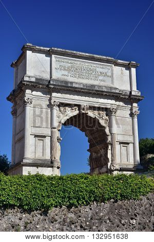 Ancient triumphal arch dedicated to Emperor Titus at the entrance of the Roman Forum behind a ruined wall (1st century A.D.)