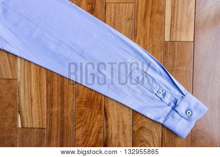 Texture of sleeve blue shirt on wooden boards