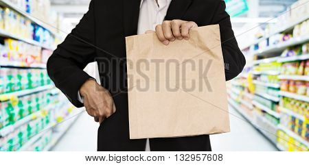 Businessman showing brown paper bag at supermarket