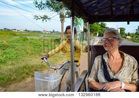 Kampong Cham, Cambodia - November 20, 2014: Cambodian boy on bicycle getting a free ride from tuk tuk