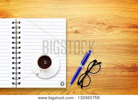 notebook with pen and glasses isolated on wood
