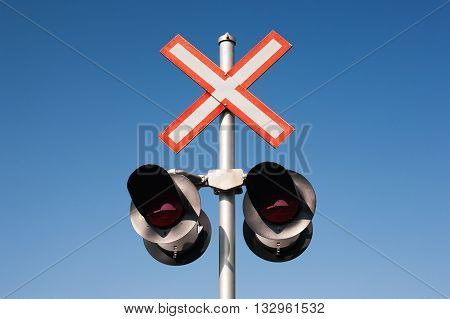 Railroad crossing signal lights and clear blue sky.