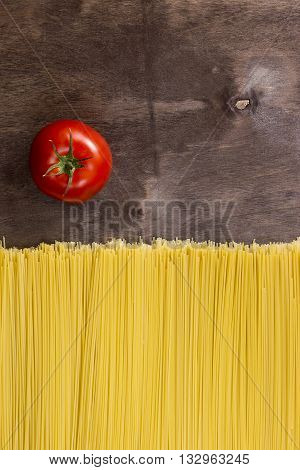 Spaghetti and tomato on a dark wooden background