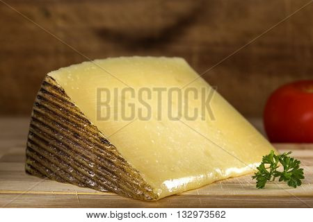 Pieces of sheep milk cheese on wooden background
