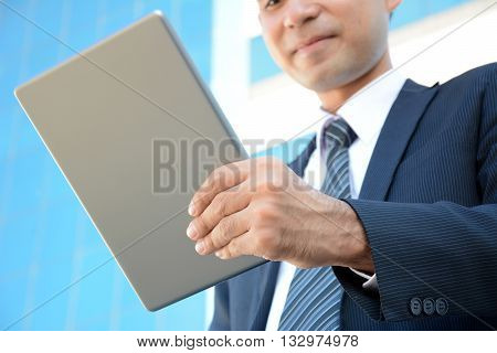 Businessman holding and looking at tablet pc